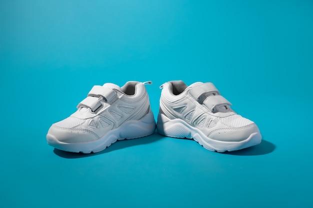Vista frontale di due sneakers bianche unisex con chiusure in velcro rivolte in direzioni diverse su un...