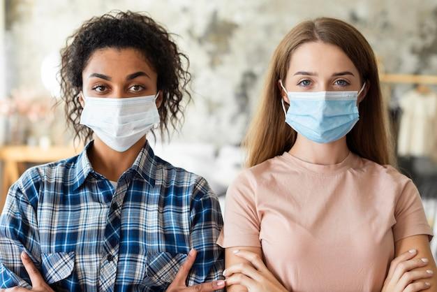 Vista frontale di due donne che indossano maschere mediche a casa