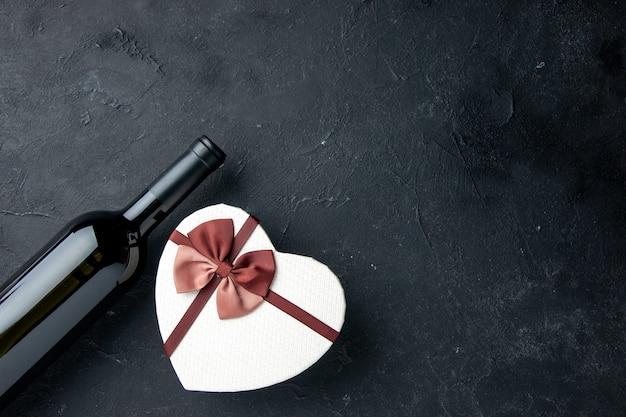 Vista frontale il giorno di san valentino presente in scatola a forma di cuore con bottiglia di vino su sfondo scuro sentimento d'amore coppia regalo colore alcol