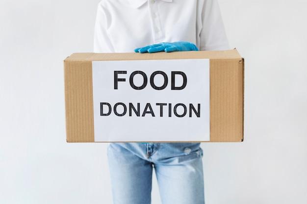 Vista frontale del volontario con guanti che tengono casella di donazione