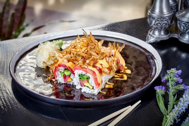 Vista frontale su rotolo caldo con tonno, salmone e uova strapazzate. suchi. stile di cibo giapponese. frutti di mare. pasto sano, equilibrato e dietetico. involtini di sushi sul piatto scuro. copia spazio, sfondo di cibo.