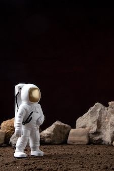 Vista frontale dell'astronauta bianco con diverse rocce sulla luna cosmica fantascienza fantasy