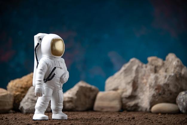 Vista frontale dell'astronauta bianco con rocce sulla luna blu cosmica fantascienza fantasy