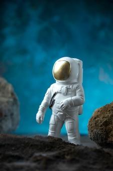 Vista frontale dell'astronauta bianco con rocce sul pavimento blu luna morte fantascienza funerale