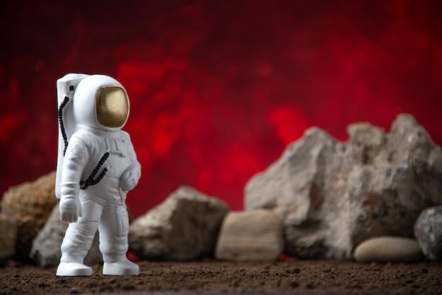 Vista frontale dell'astronauta bianco con rocce sulla luna rossa cosmica fantascienza fantasy