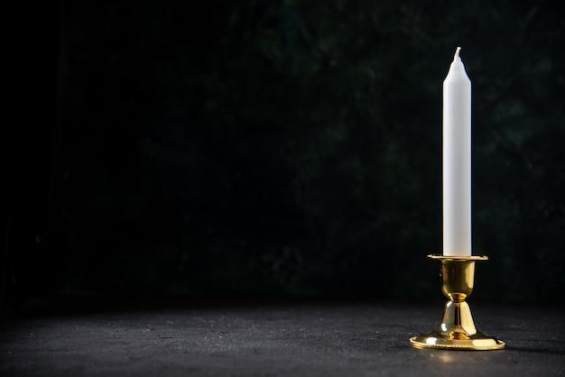 Vista frontale della candela bianca in supporto dorato sul nero