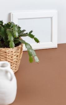 Vista frontale del mockup della cornice del poster bianco con la pianta in un vaso sopra il muro bianco