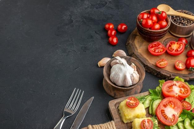 Vista frontale di verdure fresche tagliate intere e spezie su tavola di legno asciugamano bianco posate formaggio su superficie nera