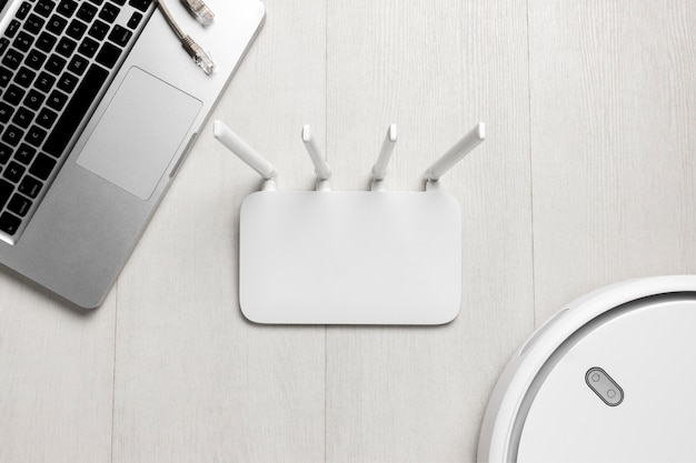 Vista frontale del router wi-fi con laptop e aspirapolvere