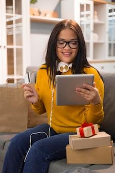 Donna di vista frontale che controlla il tablet per un nuovo acquisto