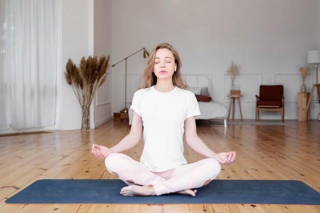 Vista frontale della donna che fa yoga a casa
