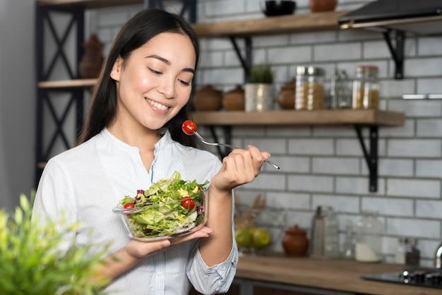 Vista frontale della donna che mangia pomodoro ciliegia con verdure verdi