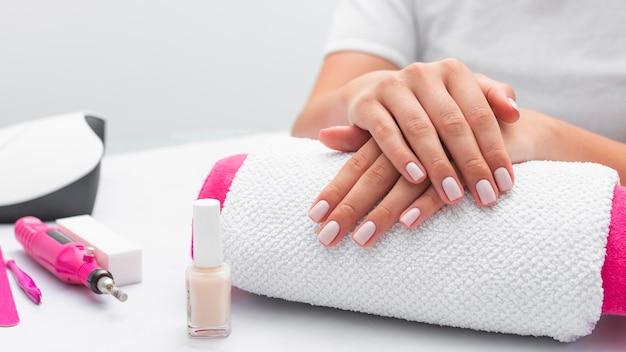 Donna di vista frontale che ottiene la sua manicure fatta al salone
