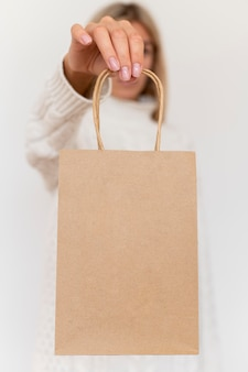 Vista frontale della donna che tiene il sacchetto di carta per il regalo di natale
