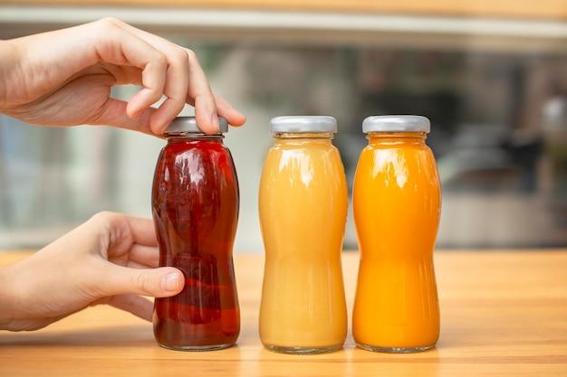 Donna di vista frontale che apre la bottiglia del succo fresco