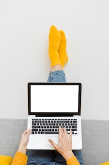 Vista frontale della donna che si siede sottosopra sul sofà mentre lavorando al computer portatile