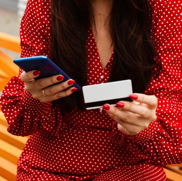 Vista frontale della donna che utilizza smartphone e carta di credito per acquistare le vendite online