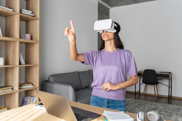 Vista frontale della donna che utilizza le cuffie da realtà virtuale a casa con il computer portatile