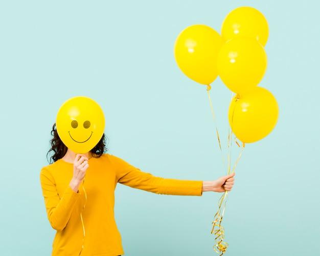Vista frontale della donna con palloncini