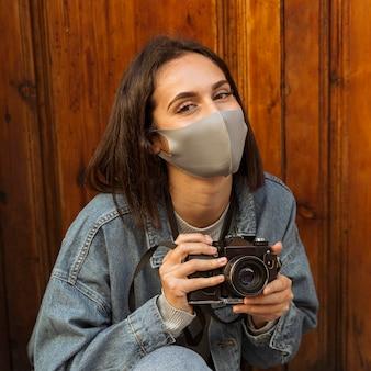 Vista frontale della donna con la maschera per il viso tenendo la fotocamera