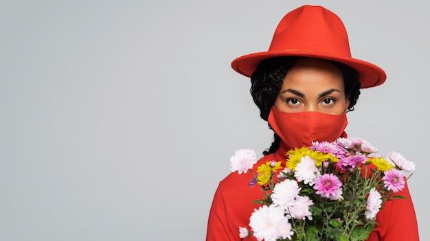 Vista frontale della donna con maschera e bouquet di fiori