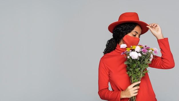 Vista frontale della donna con maschera e fiori