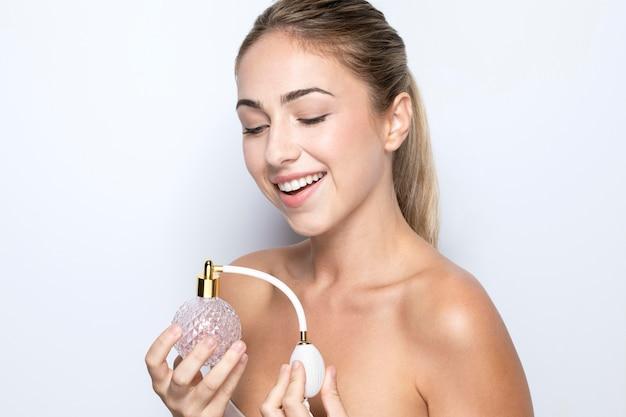 Vista frontale della donna con la bottiglia di profumo