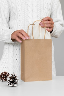 Vista frontale della donna con pigne e sacchetto di carta per regalo di natale