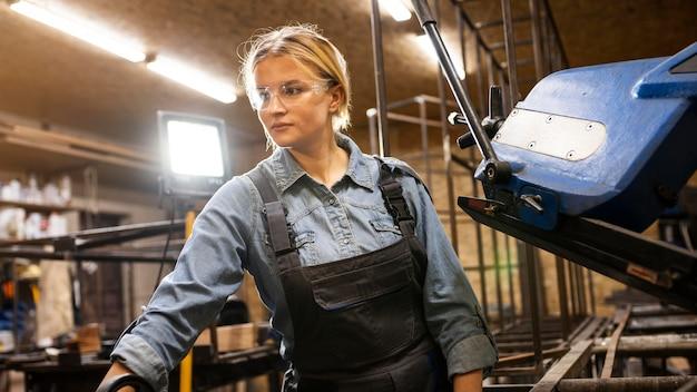 Vista frontale della donna che lavora presso l'impianto di saldatura