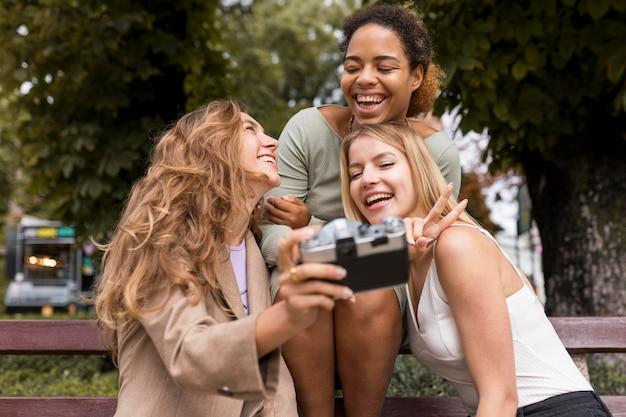 Donne di vista frontale che scattano una foto di auto con una retro macchina fotografica
