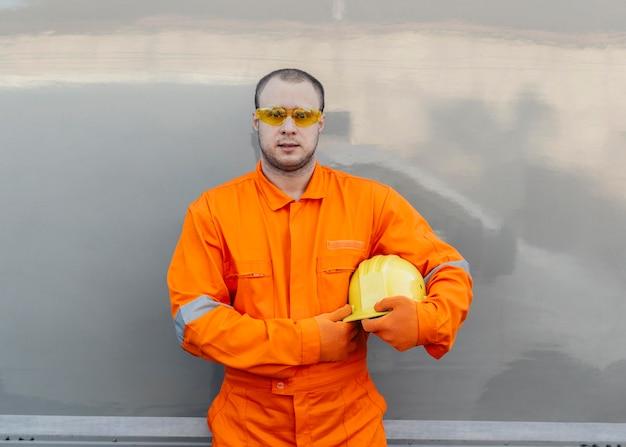 Vista frontale del lavoratore che tiene il cappello duro mentre indossa gli occhiali protettivi