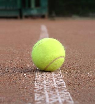 Vista frontale della pallina da tennis gialla posa all'aperto sulla linea di marcatura del campo a terra si chiuda