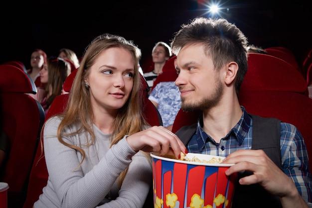 Vista frontale di giovani coppie che mangiano popcorn e che si guardano faccia a faccia durante la commedia nel teatro del cinema. ragazza bionda e uomo bello che hanno appuntamento romantico e che godono del film divertente.