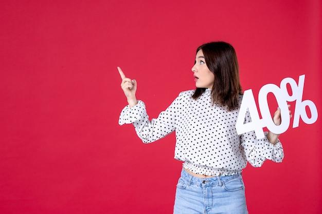 Vista frontale della giovane donna che tiene uno sconto sul muro rosso