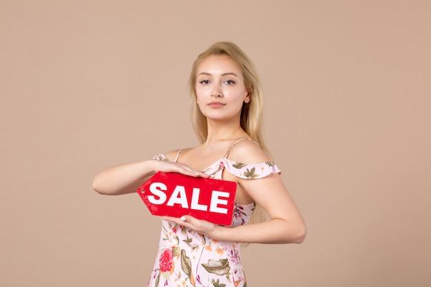Vista frontale della giovane donna che tiene il tabellone rosso della vendita sulla parete marrone