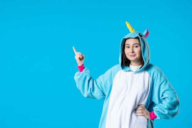 Vista frontale giovane donna in pigiama party su sfondo blu riposo dormire fino a tarda notte divertente gioco notte amici letto sogni colore