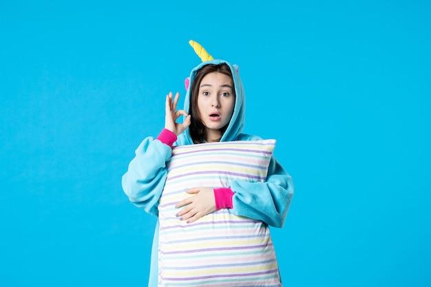 Vista frontale giovane donna in pigiama per pigiama party tenendo cuscino su sfondo blu letto riposo notturno incubo donna in ritardo divertente gioco da sogno