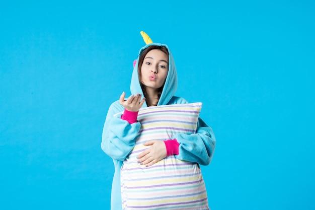 Vista frontale giovane donna in pigiama per pigiama party tenendo cuscino su sfondo blu letto riposo notturno sonno incubo donna in ritardo divertente gioco sogno bacio