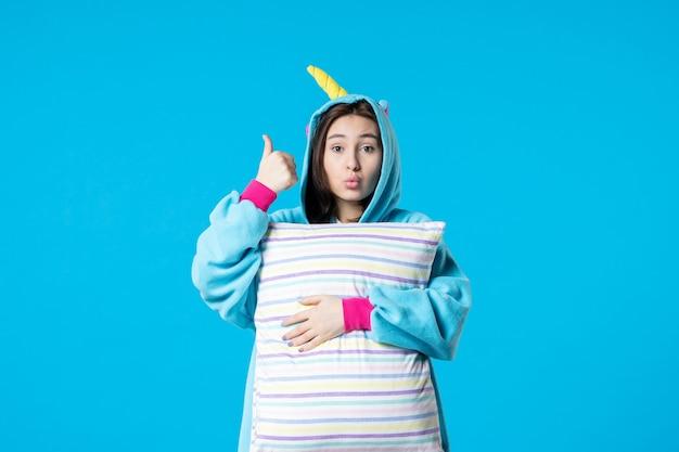 Vista frontale giovane donna in pigiama per pigiama party tenendo cuscino su sfondo blu letto riposo notturno sonno incubo donna divertente gioco da sogno