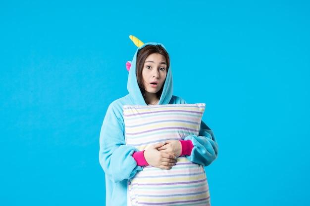Vista frontale giovane femmina in pigiama per pigiama party tenendo cuscino su sfondo blu letto donna notte riposo tardi divertimento gioco dei sogni sonno incubo
