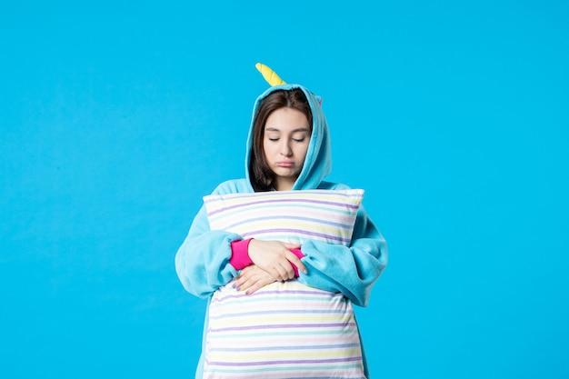 Vista frontale giovane donna in pigiama per pigiama party tenendo cuscino su sfondo blu letto donna notte riposo incubo divertimento sogno gioco sonno