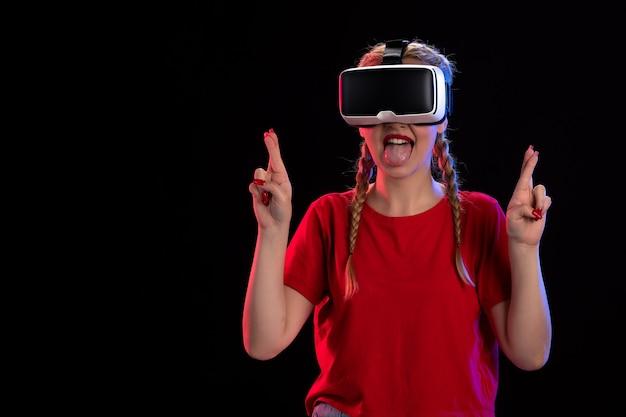 Vista frontale della giovane donna che gioca alla realtà virtuale sul muro scuro