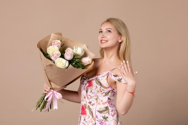 Vista frontale della giovane donna in posa con bouquet di bellissime rose sul muro marrone