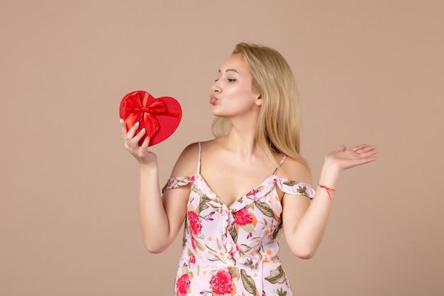 Vista frontale di una giovane donna in posa con un regalo a forma di cuore rosso sul muro marrone