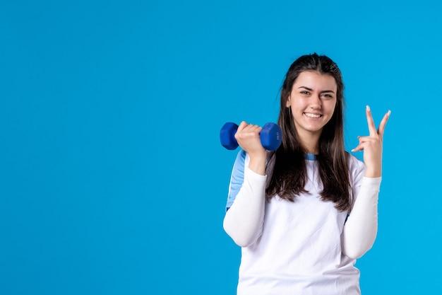 Giovane donna di vista frontale che risolve con i dumbbells blu sulla parete blu