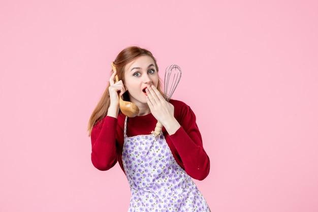 Vista frontale, giovane casalinga, presa a terra, frusta, e, cucchiaio di legno, come, telefono, su, sfondo rosa, cucina, professione, orizzontale, torta, donna, cottura, uniforme, torta, pasta