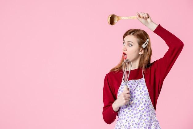 Vista frontale giovane casalinga con cucchiaio e frusta su sfondo rosa colore cottura torta torta cucina cucina pasta dolce donna