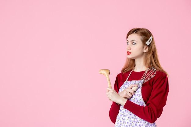 Vista frontale giovane casalinga con cucchiaio e frusta su sfondo rosa colore cottura torta cucina cucina pasta dolce cibo donna torta