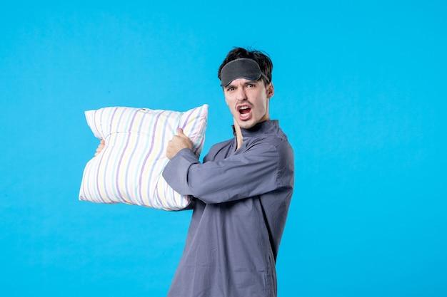 Vista frontale giovane maschio in pigiama che tiene cuscino su sfondo blu colore letto umano sogno sonno notte riposo incubo sveglia tardi arrabbiato