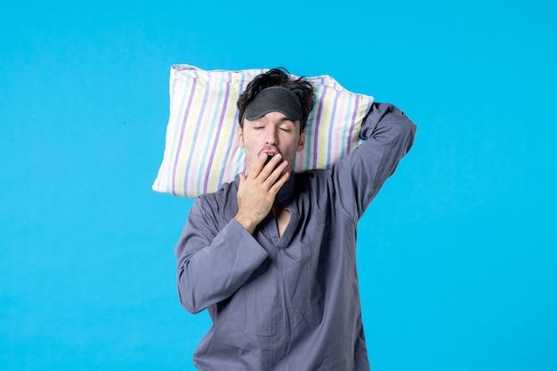 Vista frontale, giovane, maschio, in, suo, pigiama, presa a terra, cuscino, e, sbadigli, su, sfondo blu, sogno, sonno, notte, tardi, letto, resto, incubo, colore, scia, umano